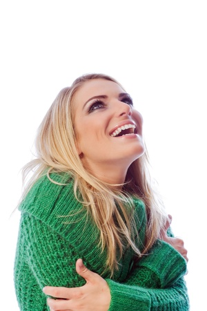 elated: Smiling young woman looking up and wearing a green sweater