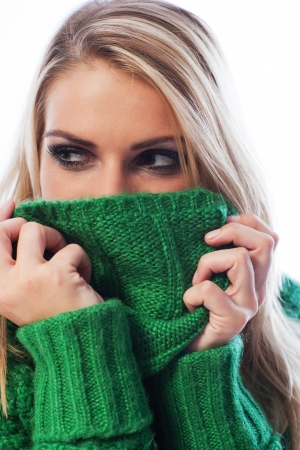 knitwear: Woman hiding her face with her green knitwear sweater collar