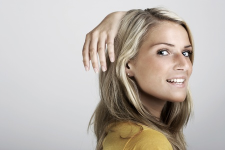 Beauty fashion portrait of a young blond woman smiling and holding the hand high behind the head Stock Photo - 20446527