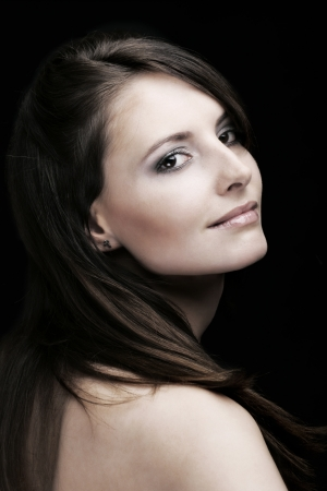 Beauty portrait of a smiling caucasian woman with long brown hairs looking back and over her bare shoulder at the camera, on a black background photo