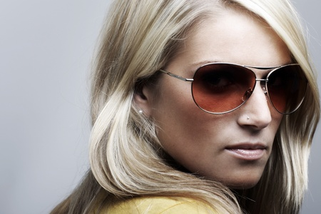 Beauty portrait of a beautiful blonde Caucasian woman wearing sunglasses, looking back and over her shoulder to the camera on a gray background photo