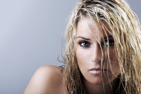 Beauty portrait of a sexy caucasian blonde woman with wet hair, blue eyes and intense expression looking at camera, on a gray background with copy-space photo