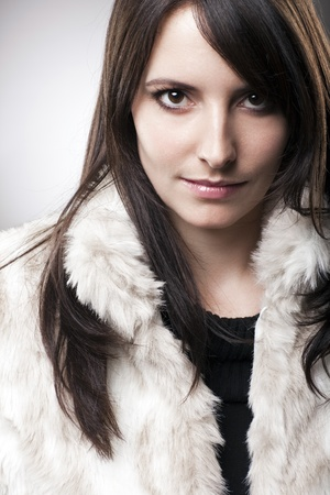 Portrait of a beautiful caucasian woman with long brown hair, looking at camera and wearing a fluffy white fur jacket photo