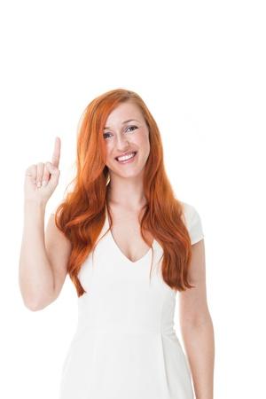 coppery: Bella donna con i capelli rossi splendidi ramato che punta con il dito alla vuoto copyspace sopra la sua testa isolato su bianco Archivio Fotografico