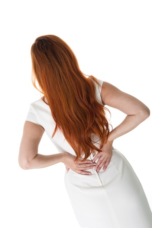 Woman with long red hair standing holding her lower back in pain, view from behind isolated on white photo