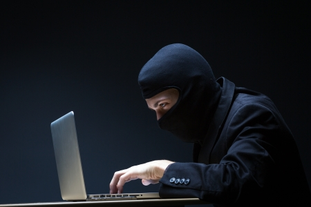 Computer hacker in a balaclava working in the darkness stealing data and personal identity information off a laptop computer Stock Photo