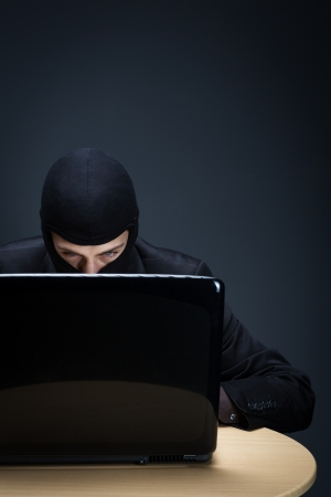 Secretive computer hacker bent closely over a computer screen in the darkness stealing important and private information, conceptual image photo