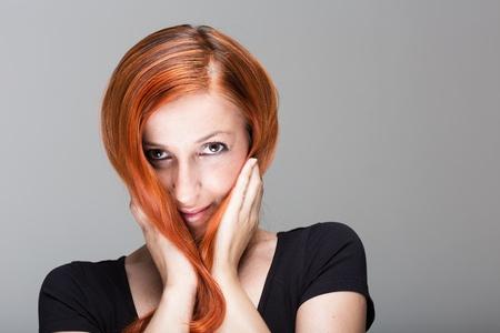 coppery: Giovane donna che gioca con i suoi bei capelli rosso rame lungo tenendolo contro le guance con le mani mentre guardando fuori verso la telecamera Archivio Fotografico