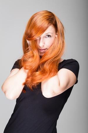 coppery: Donna con capelli rosso rame in posa con le mani al viso e capelli lunghi che scorre intorno ai polsi