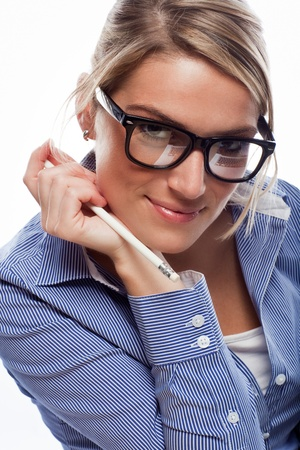 Seductive blonde caucasian businesswoman wearing glasses with retro thick frame, an unbuttoned blue shirt and holding a pencil, looking at camera, on a white background Stock Photo - 20443278