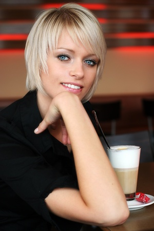 Blonde girl looking at camera with coffee photo