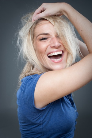 zerzaust: Sch�ne blonde lachend mit zerzausten Haaren und Spa�