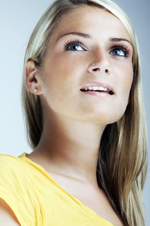 sexiness: Low angle close up portrait of a stunning young blond woman with a pensive expression and parted lips