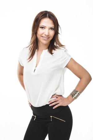 provoking: Friendly casual young woman in trendy jeans standing with her hands on her hips smiling at the camera isolated on white Stock Photo