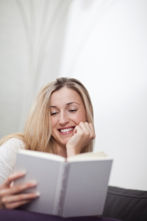 immersed: Happy relaxed young woman sitting on a sofa at home reading a book and smiling with enjoyment Stock Photo