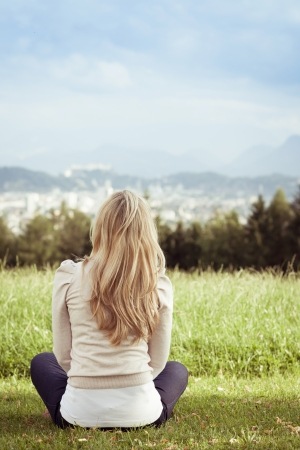 long legged: Woman enjoying a view of the town sitting cross legged in a green field with her back to the camera Stock Photo