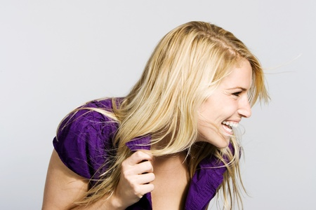 vivacious: Candid portrait of a beautiful vivacious blond woman laughing happily and looking off to the side of the frame