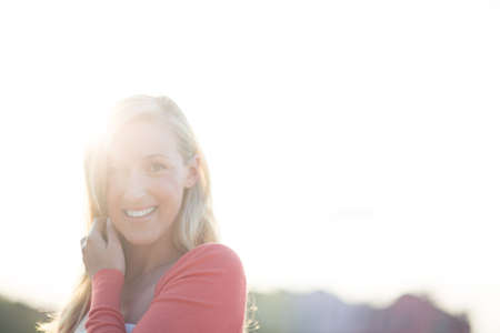 Woman enjoying a hot summer day standing smiling at the camera with a bright sunburst over her shoulder and copyspace photo
