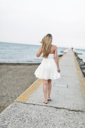 Woman taking a walk on the beach walking away from the camera in a white summer dress along a walkway on top of a sea wall photo