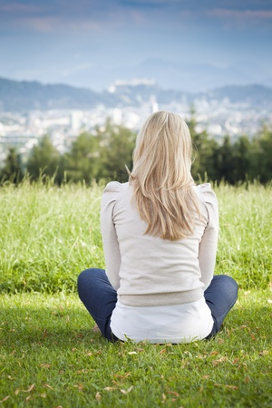 tranquillity: Rear view of a woman with long blond her sitting on the grass overlooking a distant town enjoying the tranquillity practising yoga and meditating