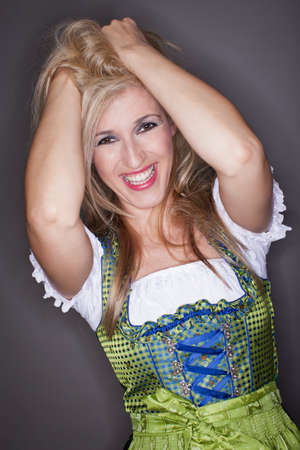 clutching: Laughing vivacious beautiful young woman with her hands raised clutching her long blond hair dressed in cool fashion in a traditional dirndl