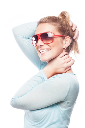 lighthearted: Light-hearted vivacious young woman with a beautiful smile wearing sunglasses isolated on white
