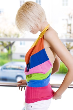 halterneck: Modern trendy woman with a short blond hairstyle posing sideways in a colourful close fitting summer dress against a high key outdoor background