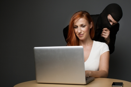 identity thieves: Man in a balaclava furtively watching an unsuspecting female office worker working on her laptop computer while corporate spying, stealing personal or business information or employee monitoring