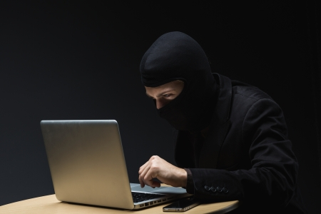 furtive: Computer criminal or hacker in a balaclava sitting at a desk in the darkness stealing information off a laptop computer and copying it onto a small hard drive