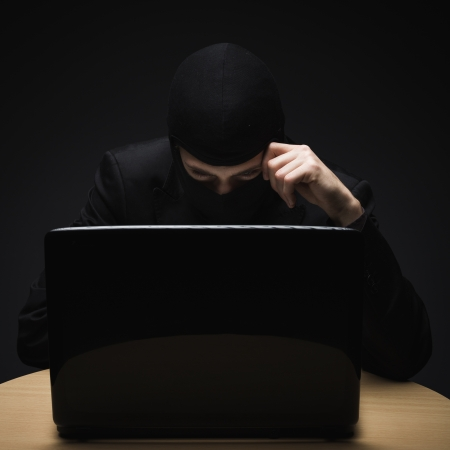 Cybercrime as a hacker disguised in a balaclava sits in the darkness behind a laptop computer stealing personal or business information photo