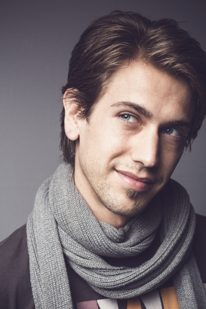 Close up portrait of a handsome young man with a thoughtful sympathetic expression wearing a warm winter scarf looking upwards