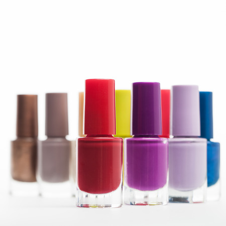 unlabelled: Twisting line of colourful unlabelled bottles of nail varnish in modern stylish fashion colours on a white background