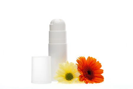 unlabelled: Beauty essentials with two unlabelled white containers for skincare products alongside two colourful fresh Gerbera daisies on a white background Stock Photo