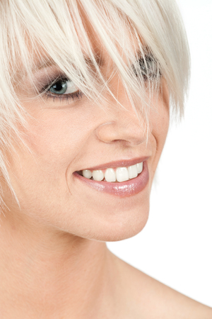 Closeup cropped beauty portrait of a beautiful woman with short trendy blond hair and a lovely smile isolated on white photo