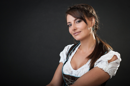Beautiful woman dressed for the Oktoberfest in a traditional dirndl and blouse looking at the camera with a gentle friendly smile, head and shoulders portrait on black with copyspace photo
