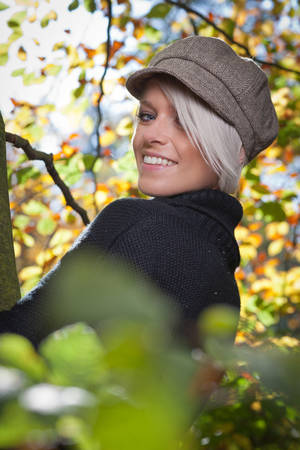 tantalising: Beautiful trendy young woman wearing a stylish cloth cap turning to look at the camera with a smile standing in autumn trees