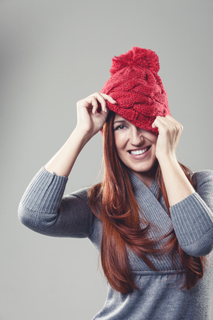 concealing: Playful attractive young woman in a knitted red beanie cap pulling it down to conceal one eye while smiling at the camera, isolated on grey