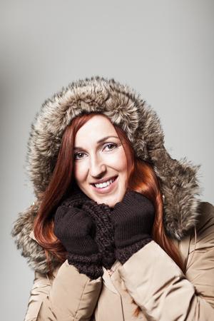 coppery: Bella donna rossa con i capelli ramati coccole gi� dentro il calore di un elegante foderato di pelliccia giacca con cappuccio indossando i guanti e sciarpa con un bel sorriso sul suo volto, su grigio con copyspace