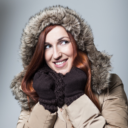 anorak: Beautiful young woman with a warm friendly smile and coppery red hair wearing a fur-lined hooded anorak, gloves and a scarf in a depiction of winter beauty