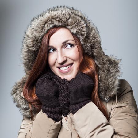Anorak: Sch�ne junge Frau mit einer warmen, freundlichen L�cheln und kupferrote Haar tr�gt einen pelzgef�tterten Kapuze Anorak, Handschuhe und einen Schal in einer Darstellung des Winters Sch�nheit