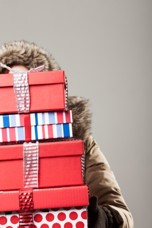holiday spending: Christmas shopping stress - a woman in a winter anorak is hidden behind a tall stack of colourful decorative Christmas presents as she returns from a day out purchasing gifts