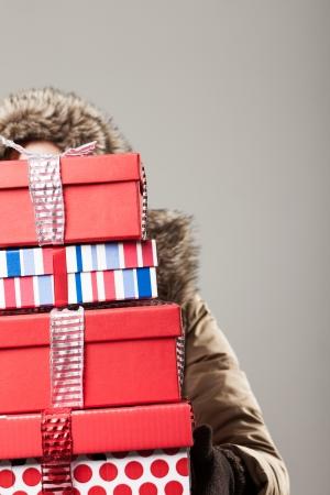 Anorak: Weihnachts-Shopping Stress - eine Frau in einem Winter Anorak ist hinter einem hohen Stapel von bunten dekorativen Weihnachtsgeschenke versteckt, als sie von einem Tag kehrt aus dem Kauf Geschenke