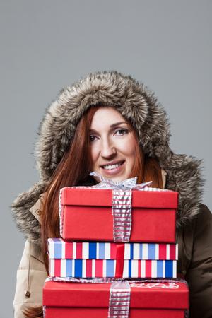 Anorak: H�bsche Rothaarige Frau Winter tr�gt einen pelzigen Kapuze Anorak mit einem Stapel von bunten Geschenk verpacken Weihnachtsgeschenke