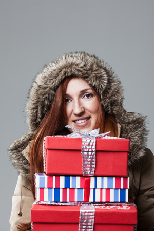 anorak: Pretty redhead winter woman wearing a furry hooded anorak carrying a pile of colourful gift-wrapped Christmas presents