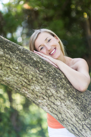contentment: Pretty young blond woman leaning on a tree trunk in a park or garden smilng at the camera in contentment