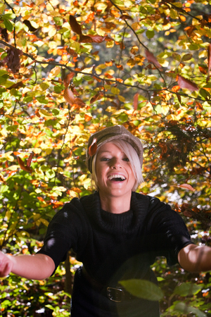 exuberant: Playful laughing young blond woman in a trendy cloth cap enjoying autumn frolicking under the colourful yellow fall leaves