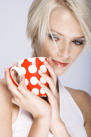 cradling: Pensive beautiful young woman with short blond hair cradling a colourful red and white polka dot mug of coffee in her hands as she looks wistfully downwards