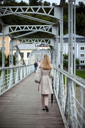 Woman in a stylish beige raincoat walking away across an urban pedestrian bridge photo