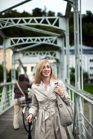 inclement weather: Stylish young blond woman in a light beige raincoat carrying a modern handbag and umbrella on a pedestrian walkway Stock Photo