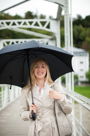 Woman out walking in the rain smiling as she shelters under her umbrella in her stylish beige raincoat photo